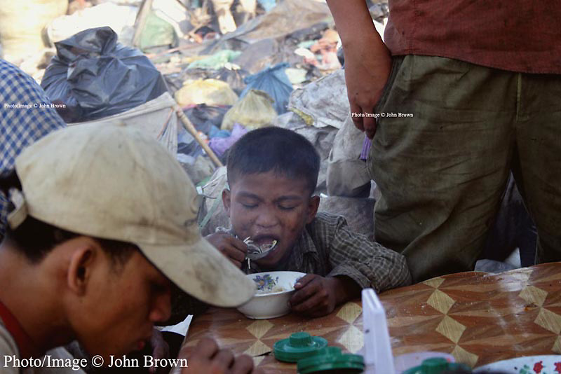 A young worker takes time out from his duties as a bottle and can collector to enjoy a meal at The Stung Meanchey Landfill in Phnom Penh, Cambodia. About 2000 people earn their livings as scavengers at the dump.