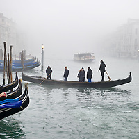 VENICE, ITALY - JANUARY 17: Peak time on the Grand Canal, e waterbus and a gondola ferry cross each other as thick fog shrouds the city on January 17, 2012 in Venice, Italy. Venice woke up this morning under a heavy blanket of fog adding to the atmosphere of the city...HOW TO LICENCE THIS PICTURE: please contact us via e-mail at sales@xianpix.com or call our office London   +44 (0)207 1939846 for prices and terms of copyright. First Use Only ,Editorial Use Only, All repros payable, No Archiving.© MARCO SECCHI