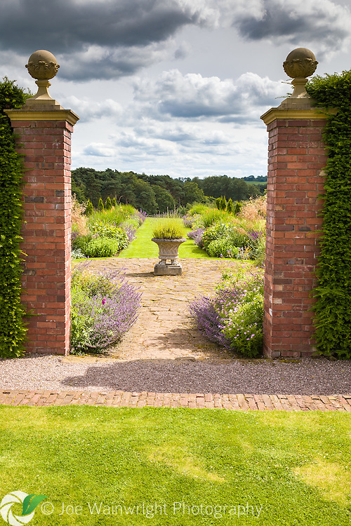 A gateway from The Pool Garden at Abbeywood Gardens, Cheshire, leads to more borders and a view of the nearby countryside.