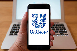Using iPhone smartphone to display logo of Unllever multinational conglomerate