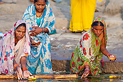 Indian Hindu pilgrims bathing and with prayer candles in The Ganges River at Dashashwamedh Ghat in Holy City of Varanasi, Benares, India