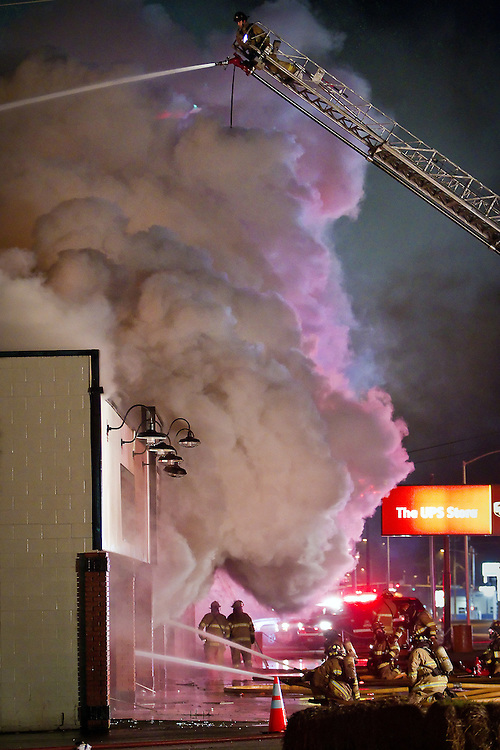 A Coeur d'Alene firefighter positions a fire nozzle toward the interior of Performance RC Hobbies at 2928 Government Way in Coeur d'Alene while trying to keep the blaze from damaging other business located within the strip mall.