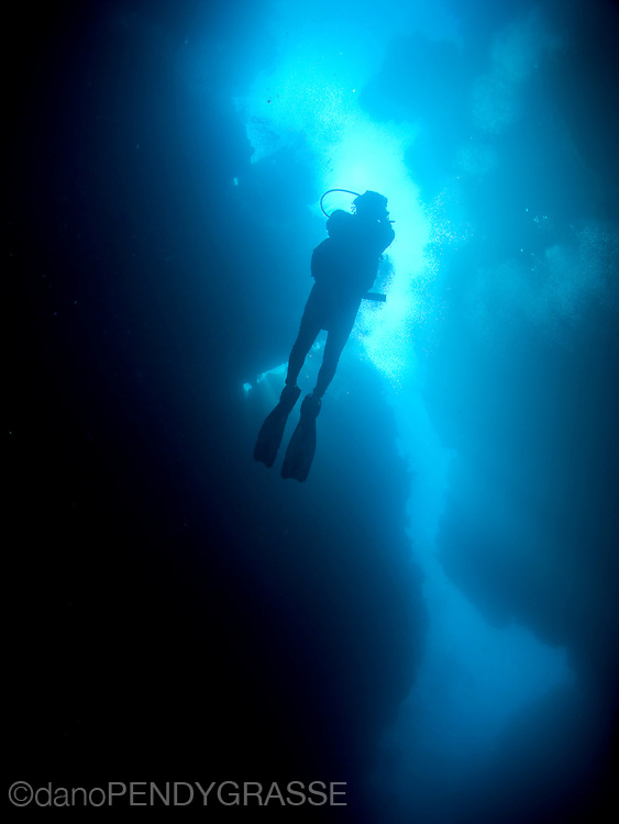"A scuba diver is seen from below in ""spooky channel"", one of the signature dives on the Honduran island of Roatan."