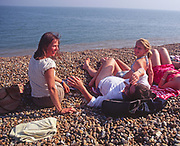 AYBR71 Woman friends and children sunbathe and chat on shingle beach summer England