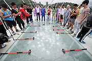 ZHANGJIAJIE, CHINA - JUNE 25:<br /> <br /> A radio broadcast is taken on glass-bottomed bridge for a safety test at Zhangjiajie Grand Canyon on June 25, 2016 in Zhangjiajie, Hunan Province of China. World\'s tallest and longest glass-bottomed bridge has been completed and took a global broadcast through television and internet medias to show its safety. More than thirty citizens and visitors thumped the bridge with hammer in the test event. <br /> ©Exclusivepix Media