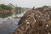 View of the Citarum river running through Kampung Bolero, Dayeuhkolot district, Bandung regency, Indonesia. Sludge and trash dredged from the riverbed is now piled up on the riverbank. <br /> <br /> The Citarum river, which runs about 270 kilometers through the province of West Java, is considered to be among the world's dirtiest. Over the last twenty years, the river has been severely polluted by toxic industrial waste, trash and raw sewage. The Citarum is one of the main sources of freshwater for West Java and supplies about 80% of water for Indonesia's capital Jakarta.