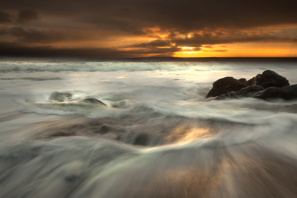 encroaching storm at rodeo beach, marin headlands, fort baker, california. long exposure photography creating a vortex shape as the water moves around rock.