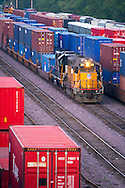 A single Union Pacific locomotive shuffles cars around in the giant Proviso Yard in suburban Chicago. Nearby tracks are jammed full of colorful ocean containers destined for the Global II intermodal terminal.
