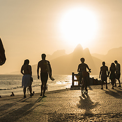 People walking the boulevard of Ipanema beach at sunset, Rio de Janeiro, Brazil.