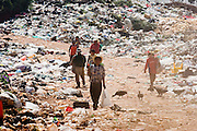 09 NOVEMBER 2004 - TAPACHULA, CHIAPAS, MEXICO: People walk to work through a flock of vultures in the municipal garbage dump in Tapachula, Chiapas, Mexico. About 130 people, the poorest of the poor in Tapachula, work in the dump picking through the garbage hoping to find tidbits they can use or sell to brokers who sit on the edge of the dump and resell the garbage. Most of the dump workers are Guatemalan migrants who crossed the border hoping, at one time, to get to the United States. Now they have settled for an existence on the very edge of Mexican society. PHOTO BY JACK KURTZ