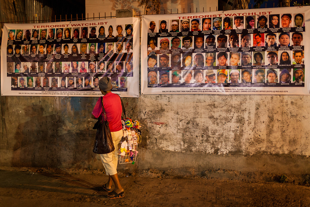 Davao City, Mindanao, Philippines - JUNE 18: A visitors is seen examining two large posters of Wanted Terrorist posted at the Roxas Night Market.  Roxas Night Market was bombed on September 16, 2016.  14 people were killed and 70 were injured and three men who are linked to the Maute Group were arrested for the bombing.