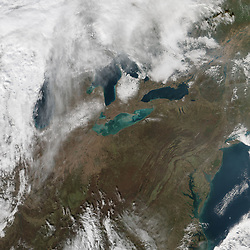 "November can be a stormy month in the Great Lakes region, as it was again in 2015. Toward the middle of the month, a low-pressure system and cold front swept up from the Central Plains and across the lakes. In Detroit, media outlets reported wind gusts as high as 52 miles (84 kilometers) per hour that left 13,000 residents without power. On Lake Erie, gale force winds halted shipping.<br /> Winds were not the only reason ships sought safe anchorage. The high winds created a seiche - a large standing wave that occurs when strong winds and a quick change in atmospheric pressure push water from one end of a body of water to the other, according to NOAA. Seiches occur periodically on Lake Erie. In 1844, a 22-foot seiche breached a sea wall with deadly consequences. In 2008, Buffalo was flooded by waves that measured 16 feet. That's about the height of the seiche measured by a buoy at the lake's east side on November 12, 2015.<br /> Two weeks after the seiche, its effects were still evident. On November 25, 2015, the Visible Infrared Imaging Radiometer Suite (VIIRS) on the Suomi NPP satellite acquired this natural-color image of colorful green and tan swirls.<br /> ""The seiche stirred up a lot of sediment,"" said Kevin Czajkowski, a remote-sensing scientist at the University of Toledo. Not all of the colorful swirls are necessarily the result of resuspended sediments. ""I wonder if Lake Erie is having a whiting event as well.""<br /> Particles of calcium carbonate in the water can cause lightening, or ""whiting,"" of the water. That usually happens in response to changes in the water temperature, or due to increased photosynthesis by phytoplankton and other microscopic marine life.<br /> But Thomas Bridgeman, an environmental scientist at the University of Toledo, agrees that the swirls of color are mostly due to sediments. ""Little patterns along the shoreline suggest wind-driven sediment resuspension,"" he said. ""There is an olive-green tint to part of the image that might be a diatom bloom, but I think t"
