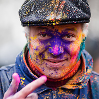London, UK - 23 March 2013: a man paints his face with colored powder during the Holi Spring Festival of Colour that takes place at Orleans House Gallery in Twickenham. The annual event marks the end of Winter and welcomes the joy of spring. This year it took place under heavy weather conditions.