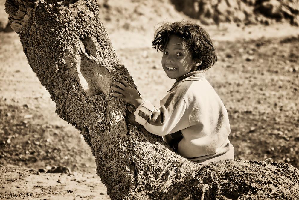 Child sitting on Tamarisk trunk.