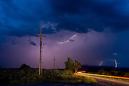 Cloud-to-cloud lightning in sky over power lines with distant cloud-to-ground lightning from separate storm cell and automobile tail light streaks along roadway, © 2014 David A. Ponton