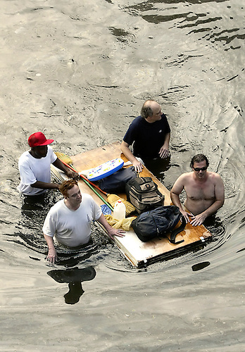 A Group Of Men With Their Belongings Placed On A Floating Door Are Being  Evacuated From.