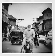 Bearded elder navigates bicycle through the traffic of Srinagar, Indian Administered Kashmir.