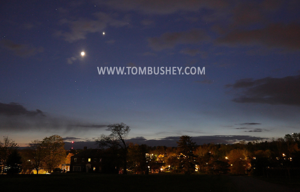 "Middletown, New York - The moon and the planet Venus, to the upper right of the moon, shine in the twilight sky over a house on April 24, 2012. The ""V"" shape of the constellation Taurus in below the moon."