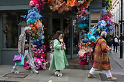 Stylish people walk past the flowers that decorate the exterior of a cafe on Brewer Street in the heart of Soho in the West End, on 18th February 2020, in London, England.