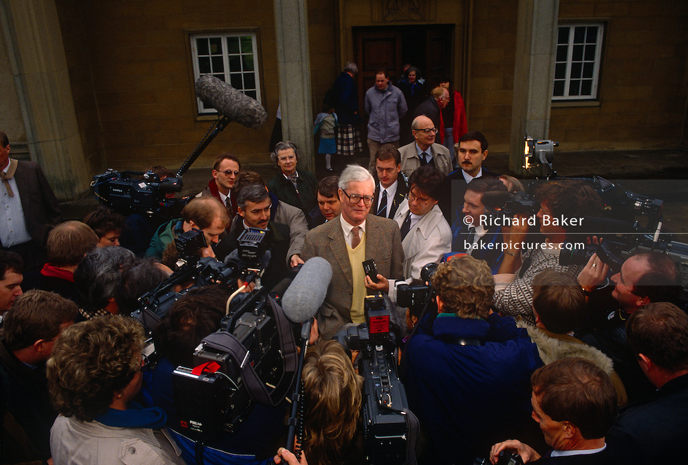 Douglas Hurd MP confronts media outside his Mid Oxfordshire constituency office during his leadership bid for the Conservative party on 23rd November 1990, at Witney England. The 1990 Conservative Party leadership election took place on 20 November 1990 following the decision of former Defence and Environment Secretary Michael Heseltine to challenge Margaret Thatcher, the incumbent Prime Minister, for leadership of the Conservative Party. Douglas Richard Hurd, Baron Hurd of Westwell, CH, CBE, PC (b1930) is a British Conservative politician who served in the governments of Margaret Thatcher and John Major from 1979 to 1995.