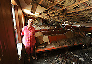 Photo by Gary Cosby Jr.    Mamie Jones lost her church and her house in the April 27th tornado.  Jones stands inside what remains of the Full Gospel Holiness Tabernacle, the church she founded and has shepherded ever since.  The building is destroyed but Jones's faith will see it rebuilt.