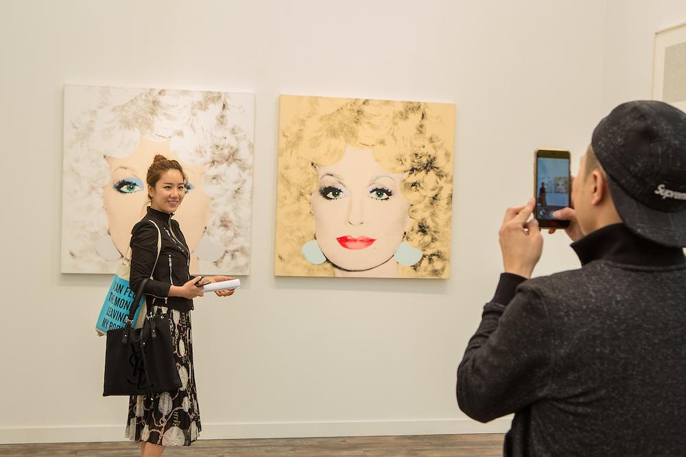 New York, NY - 6 May 2016. Frieze New York art fair. Visitors to Aquavella with Andy Warhol's Dolly Parton.