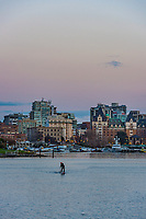A lone paddleboarder rides out into the Inner Harbour of Victoria, BC on a warm fall evening.