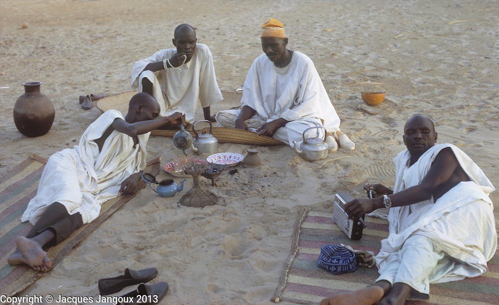 Africa, Sahel region, Chad, islands of Lake Chad, Buduma tribe: men sitting around drinking tea; note islamic prayer beads and transistor radio.