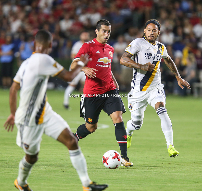 Manchester United Henrik Mkhitaryan, center, drives the ball against Los Angeles Galaxy during the second half of a national friendly soccer game at StubHub Center on July 15, 2017 in Carson, California. The Manchester United won 5-2. AFP PHOTO / Ringo Chiu
