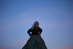 © Licensed to London News Pictures. <br /> 20/06/2014. <br /> <br /> Castlerigg Stone circle, Cumbria, England<br /> <br /> A young girl plays on one one of the ancient stones at the ancient site of Castlerigg Stone Circle near Keswick in Cumbria on the evening of the Summer Solstice.<br /> <br /> Photo credit : Ian Forsyth/LNP