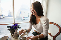 Smiling young woman having coffee at cafe