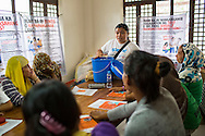 Pregnant women and lactating mothers learn about the SPRINT-IPPF dignity kit at a RH Medical Mission in the Taluksangay Barangay Hall, Zamboanga, Mindanao, The Philippines on November 5, 2013. These Internally Displaced People (IDP) had taken refuge in this Barangay (neighbourhood) after surviving the 3 week long attack by MNLF rebels. Photo by Suzanne Lee for SPRINT-IPPF