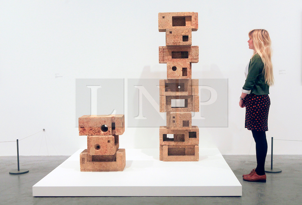 © Licensed to London News Pictures 16/04/2013.A gallery assistant at Tate Modern examines one of the main exhibits, 'Infinite Structure', that is part of the Saloua Raouda Choucair exhibition..London, UK.Photo credit: Anna Branthwaite/LNP
