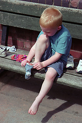 Nursery school boy sitting on bench in playground putting on socks and shoes,