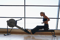 Women Using Rowing Machine in health club side view