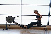 Women Using Rowing Machine in health club side view