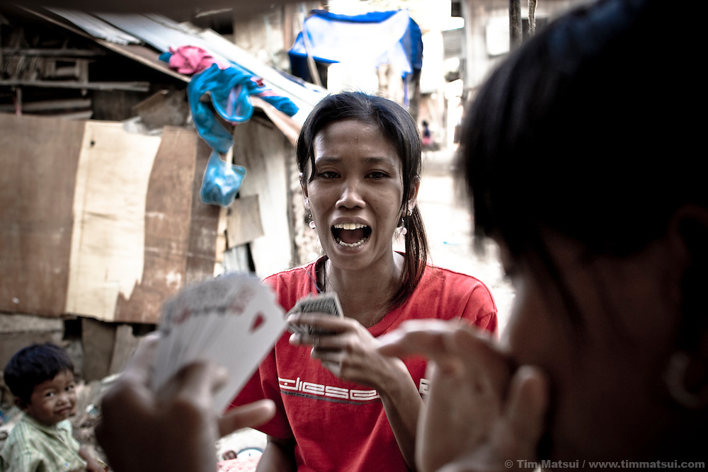 Women play cards before during the day. They live in a slum known for gangs, pimps, prostitutes, and high rate of HIV.