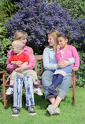 Two single mothers sitting on park bench with young children,