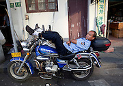 A security guard reclines upon his motorcycle.
