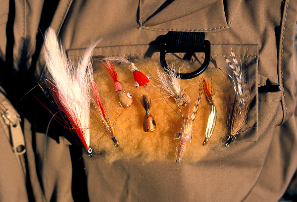 Stock photo of fly fishing lures on a fisherman's vest