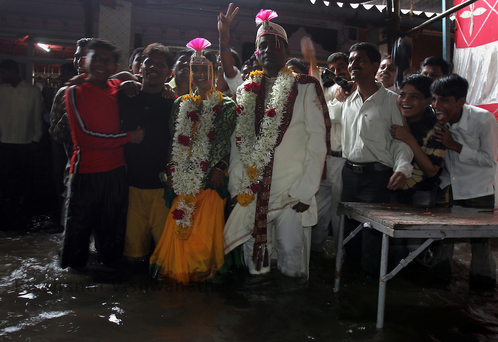 A bride and groom pose for photographs after marriage ceremony in a flooded hall due to heavy rains in Mumbai, India, on Sunday, June 24, 2007. Photographer:  Prashanth Vishwanathan/Atlas Press