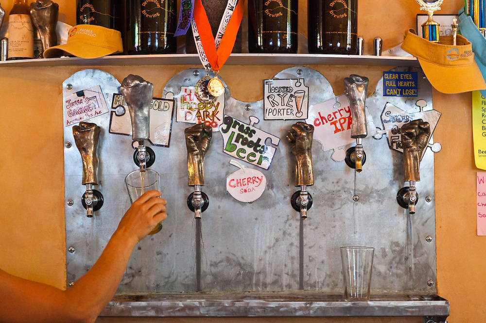 A bartender fills a pint glass from the taps at Revolution Brewing in Paonia, Colorado