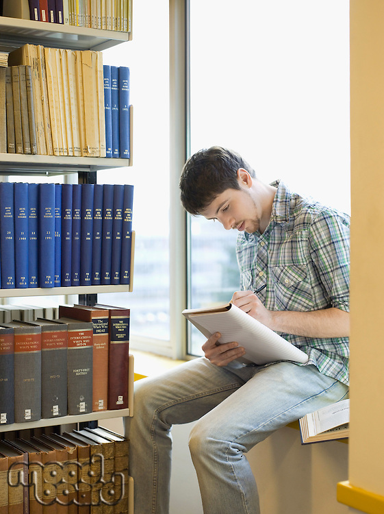 Student sitting on windowsill in library taking notes