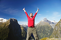 Woman with arms raised on top of mountain peak