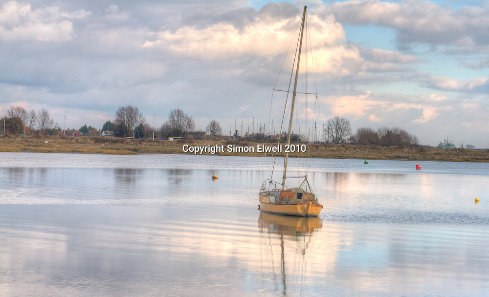 Boat on a winter mooring near Maldon with reflections on the water