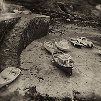 Small fishing boats in Boscastle harbour, Cornwall, England, UK with old steps on harbour wall