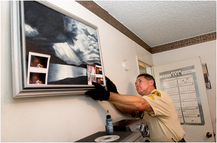 Michael Stenerson / Staff Photographer.Detective Tim Jimerson searches for drugs and weapons at a home in Adelanto Thursday during a search warrant sweep.