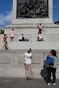 Young tourists play on the plinth of Nelson's Column in Trafalgar Square, on 10th August 2017, in London, England.