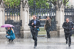 London, UK. 6 June, 2019. Members of the public seek shelter outside the Palace of Westminster during a sudden rain shower. Scattered showers are forecast for the remainder of the day, with heavy rain to follow tomorrow.