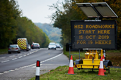 © Licensed to London News Pictures. 23/10/2019. GREAT MISSENDEN, UK.  Enabling works to allow the construction of the HS2 railway continue despite the future of the project being reviewed. A number of mature trees were due to be felled last week to allow easier access for construction traffic but local residents and climate activists created a makeshift camp to prevent their destruction.. In this picture: Road sign on the A413 warning of 19 weeks of roadworks. Photo credit: Cliff Hide/LNP